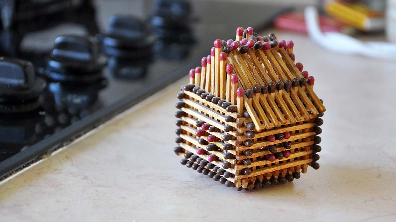 Concept art of a house made out of matches illustrates the fire damage insurance claims process